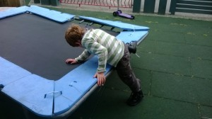 Child climing onto a trampoline