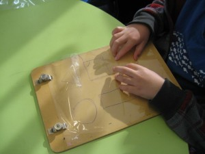 Child's hands on wooden board with 2-D shapes