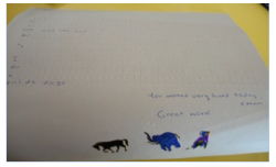 A page of braille with animals at the bottom