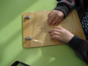 James hands locating shapes on 2D wooden board