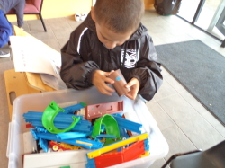 Bradley sitting infront of a box full of toy train pieces, looking closely at a toy train.
